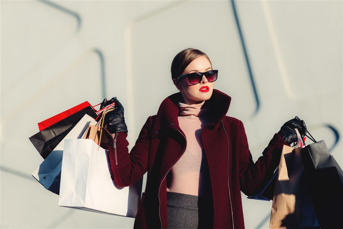 kvinde iført solbriller med indkøbsposer i hænderne