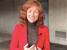 Smilende rødhåret kvinde i rød jakke