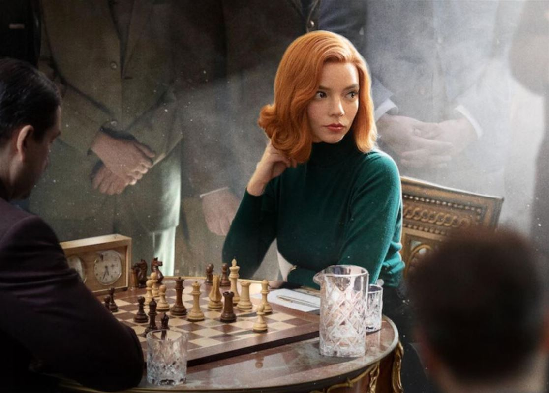 En smuk ung rødhåret kvinde ved et skakbord