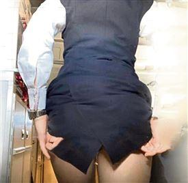 En kvinde trækker op i sin kjole i et fly