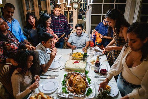 En familie samlet om et bord og en stor kalkun