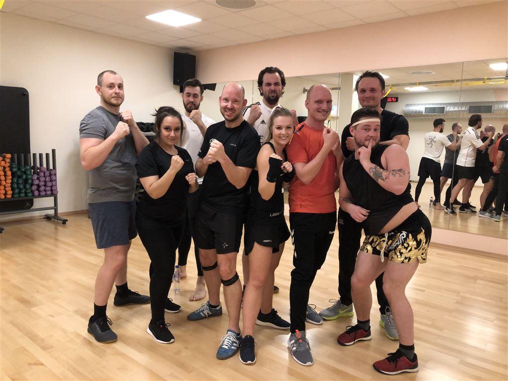 En flok almindelige mennesker i træningstøj i en gymnastiksal med spejl for enden