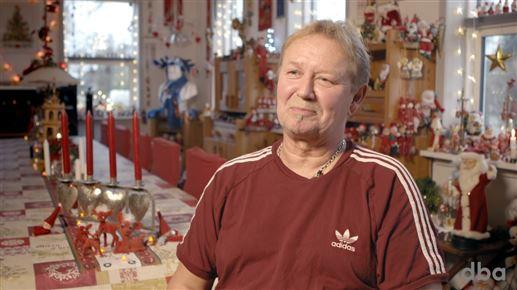 En mand foran et spisebord og en stue proppet med  nisser og julepynt