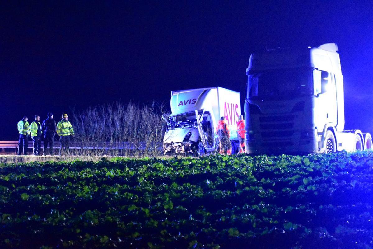 En hvid varevogn smadret ved siden af en lastbil på en mørk landevej