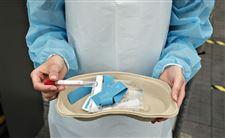 En sygeplejerske med engangskittel viser et blodprøvekit. Det ligger i et papbækken. Hun holder blodprøveglasset i din ene hånd.
