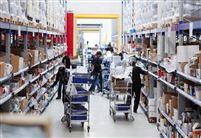 Mange medarbejdere går rundt i en lagerhal med hver sin vogn og pakker varer.