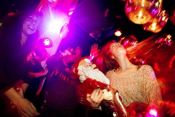 En kvinde danser på et diskotek med en havenisse på armen. Hun svinger med håret.