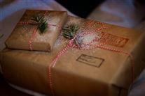To julegaver der er pakket ind i brunt gavepapir. Den nederste har to stempler på.