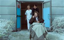 Ghita Nørby i en kørestol med cigar på vej ud fra et hospital