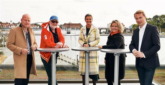 Thomas Blachman, Peter Aalbæk, Margrethe Vestager, Stine Bosse og Morten Messerschmidt står ved cafeborde ved havn