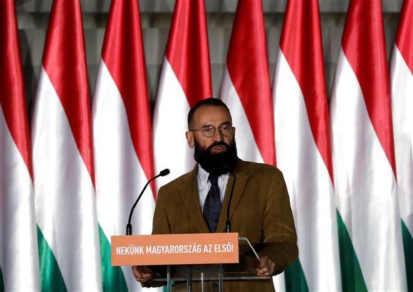 mand holder tale fra talerstol med flag i baggrunden