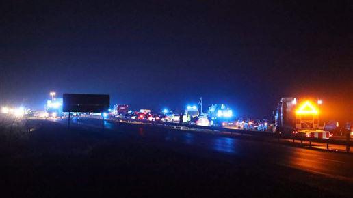 Mange udrykningskøretøjer og biler holder på en motorvej.