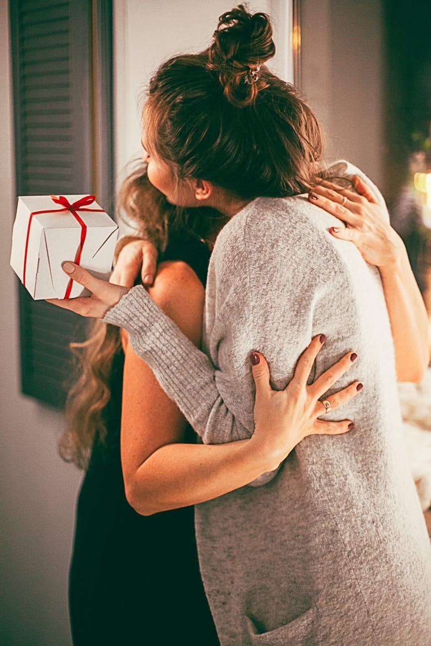 To unge kvinder giver hinanden et knus - den ene med en pakke i hånden