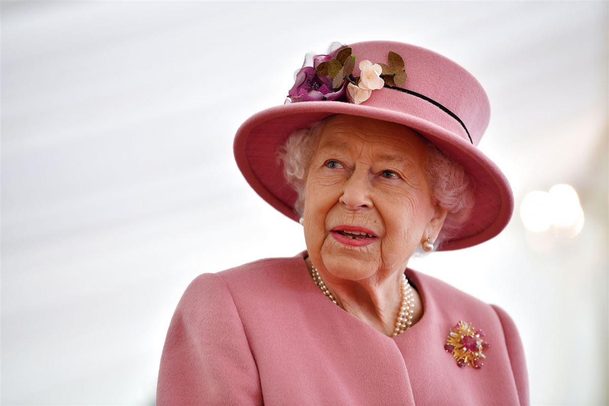 Dronning Eliabeth med rød dragt og hat.