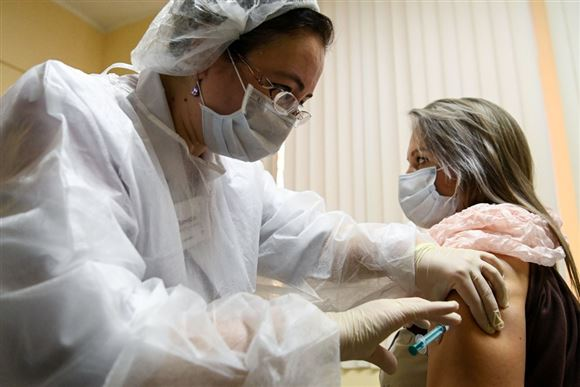Læge giver vaccine til patient.