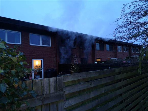 Et rækkehus med røg ud fra