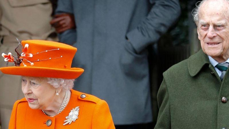 dronning elizabeth med orange hat sammen med sin mand prins hilip i grøn jakke