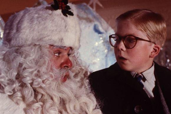 en lille dreng med briller kigger forfærdet på en julemand