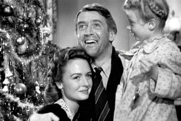 en lille glad familie foran et juletræ