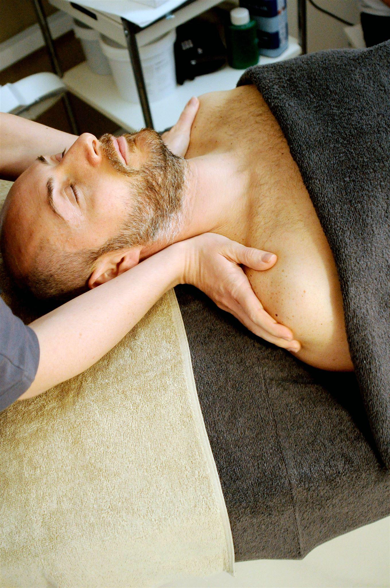 En mand på en briks får massage ved skuldrene