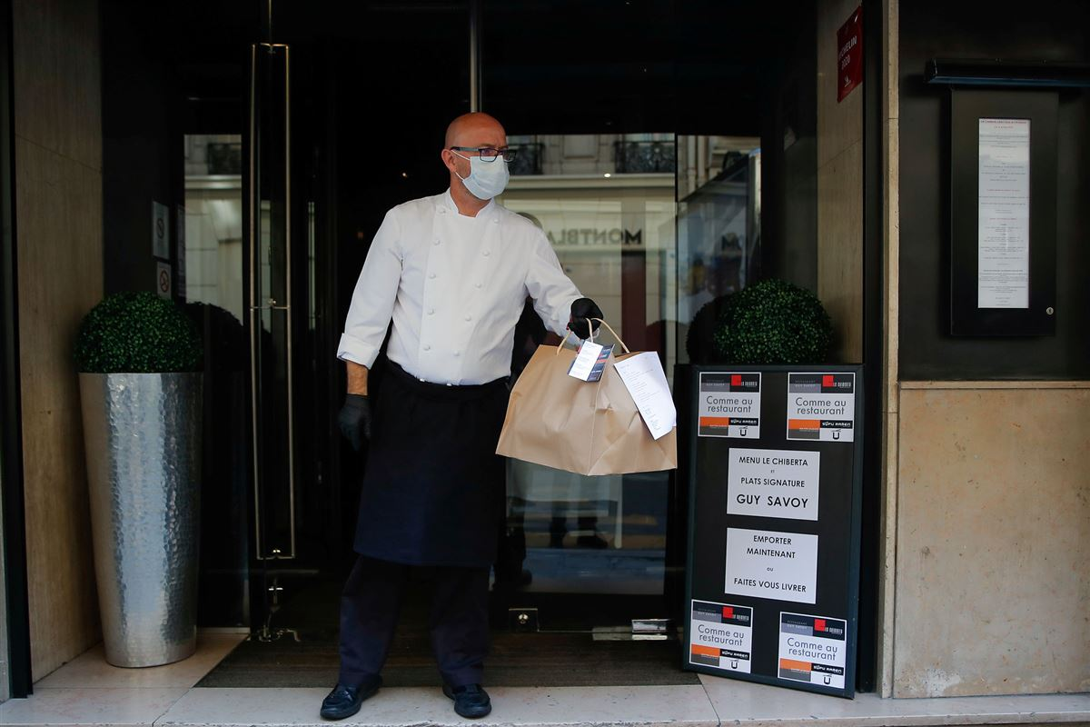 mand med mundbind foran restaurant med pose i hånden