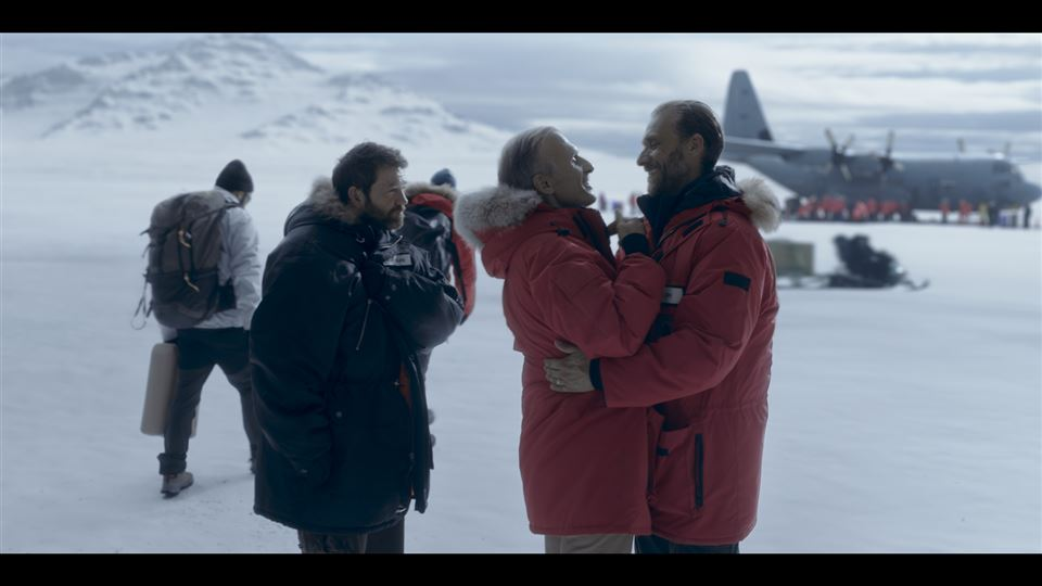 Nogle mennesker på en isfyldt natur med et Hercules-fly i baggrunden