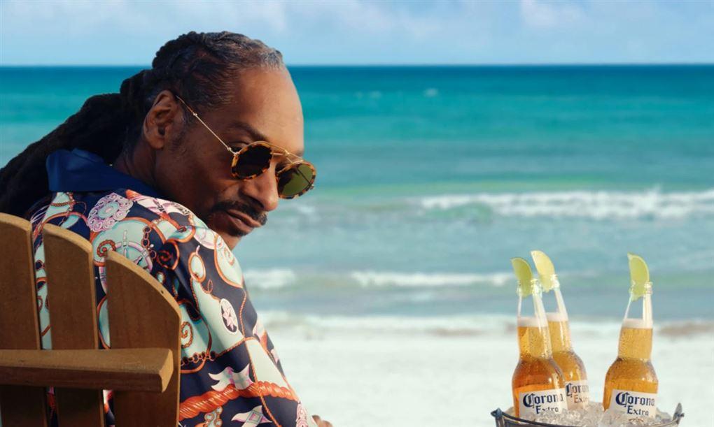 Snoop Dogg i en strandstol med nogle Corona-øl ved siden af
