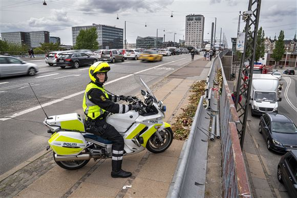 en motorcykelbetjent holder på fortovet på Langebro