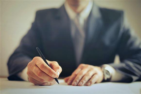 mand ved skrivebord underskriver dokument
