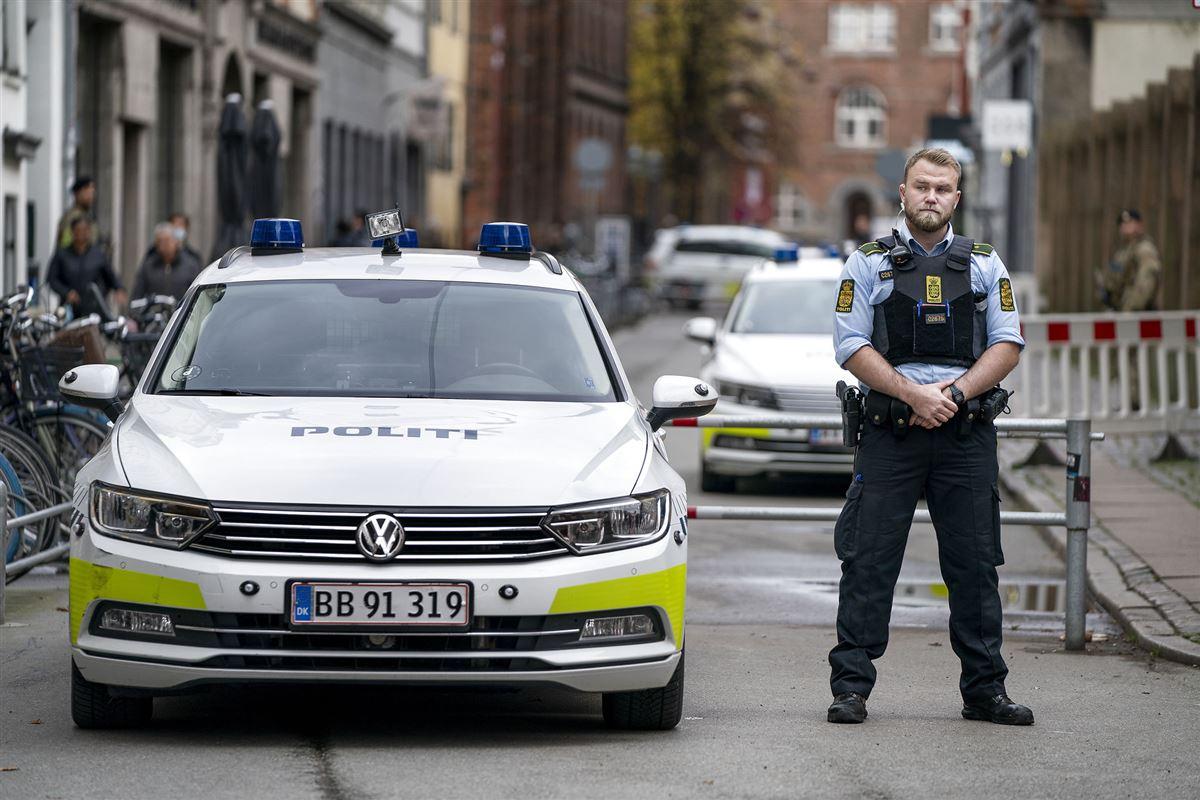 politibetjent står på gaden ved siden af politibil