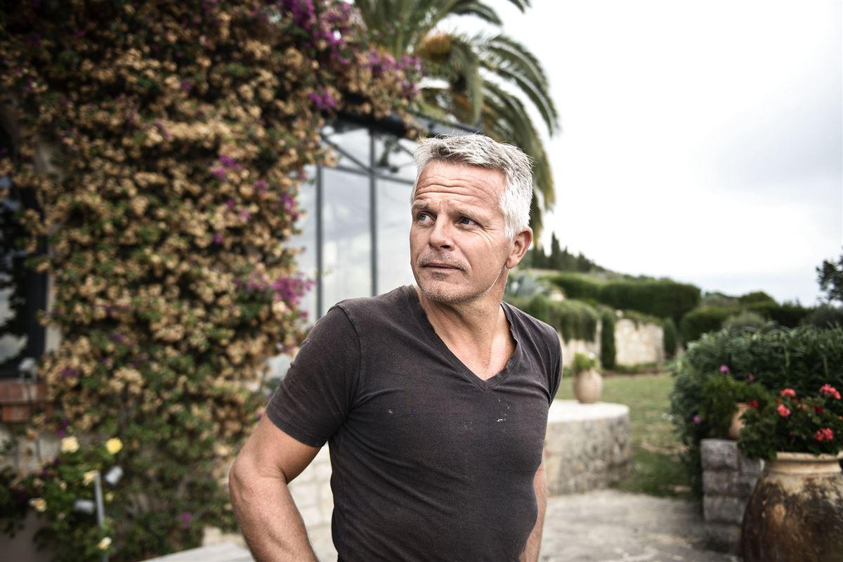 Jakob Kjeldberg foran sit hus i Sydfrankrig med en palme