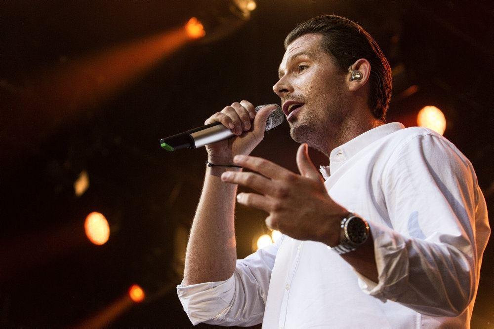 Rasmus Seebach står på scene med mikrofon i hånden