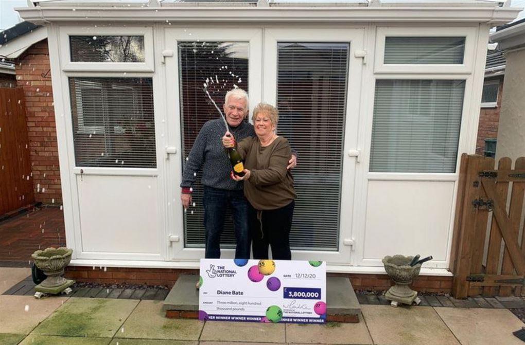 Et ældre par med champagne og en stor check foran deres hus