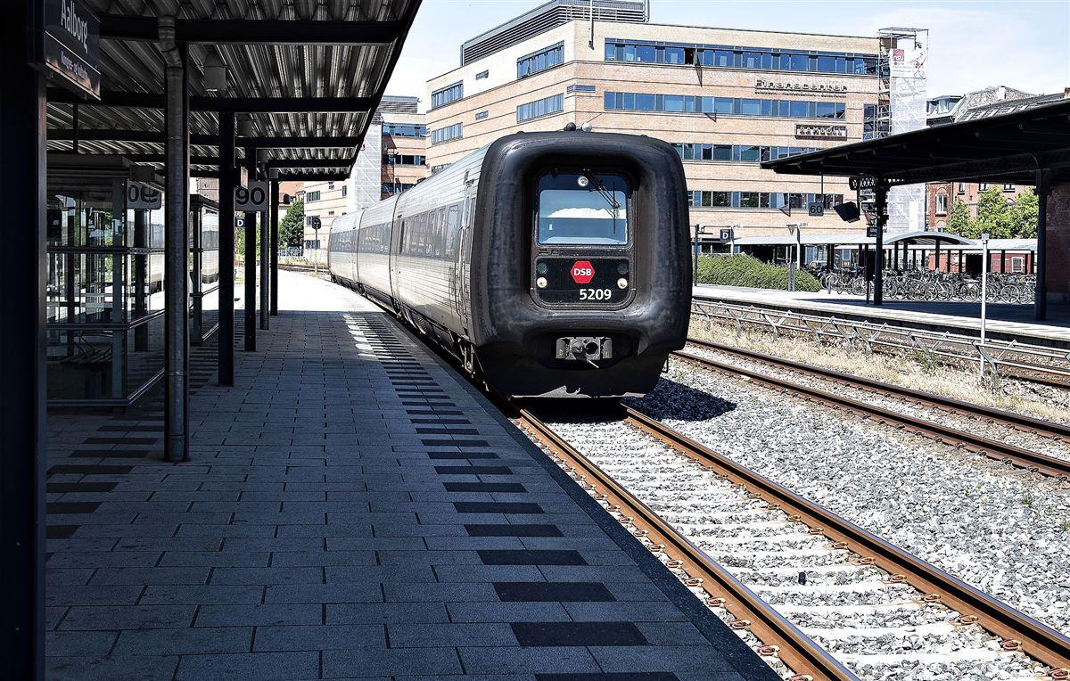 Et IC3 tog kommer kørende ved en perron.