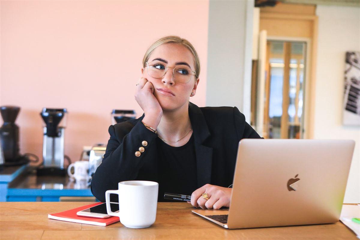 Eftertænksom kvinde med Mac og en kop kaffe.