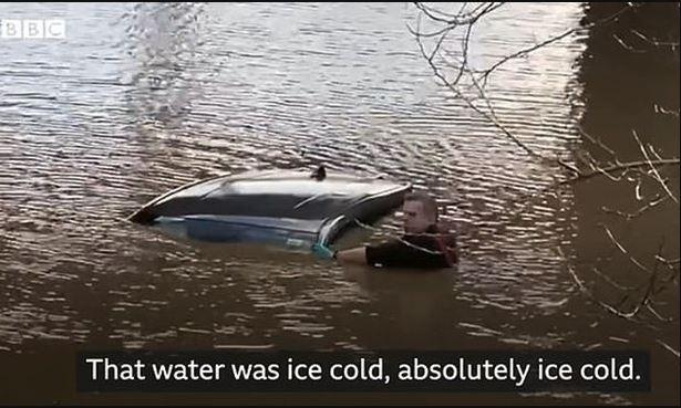 Mand ved oversvømmet bil.