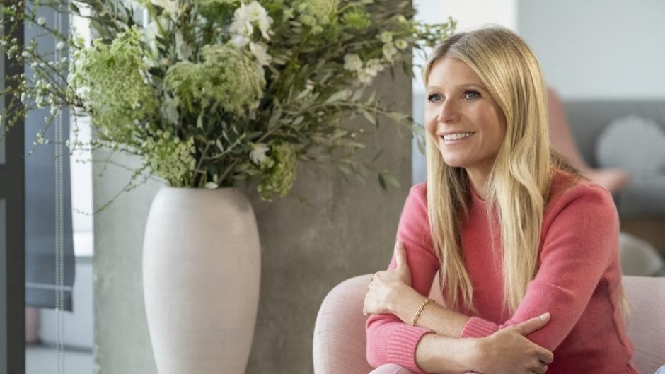 Gwyneth Paltrow i en rød tætsiddende bluse smiler
