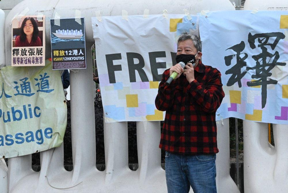 En kineser med et mundbind foran bannere