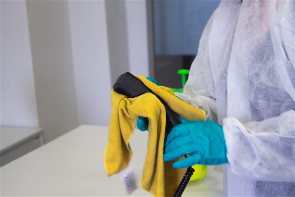 En handskeklædt rengøringsassistent afvasker et telefonrør