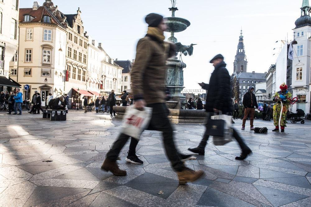 folk går på gågade med plastikposer i hånden