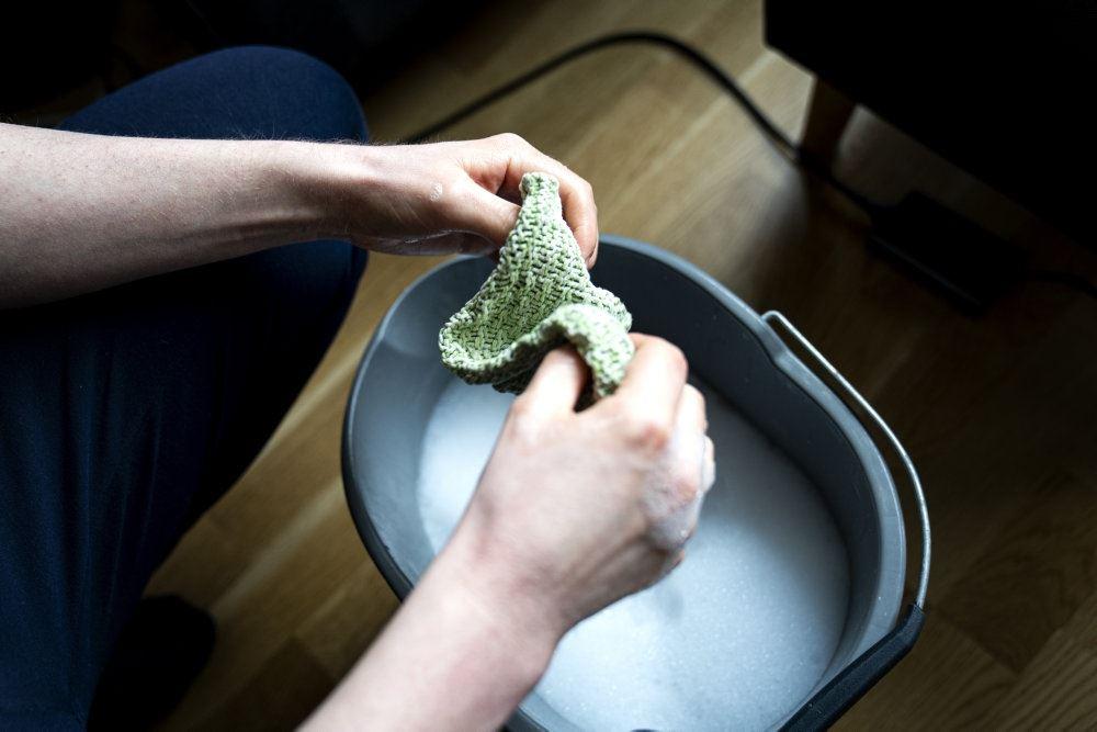 kvinde vrider klud over spand
