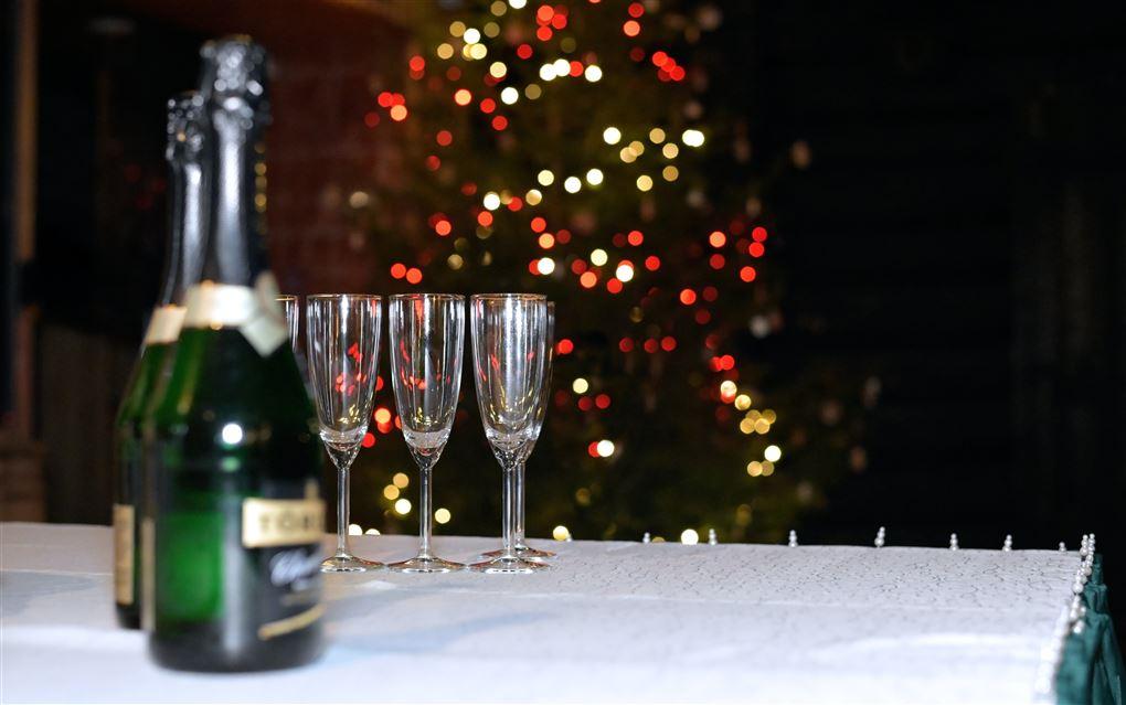 champagneflasker og glas på bord med fyrværkeri  baggrunden