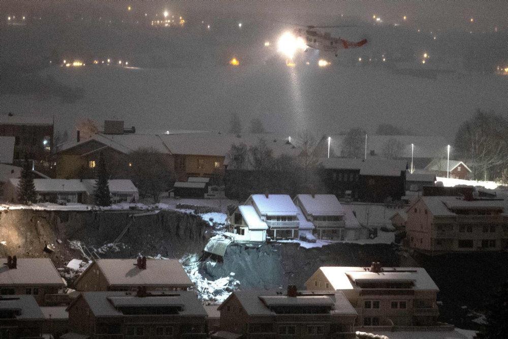 en helikopter flyver over et stort krater med huse omkring det