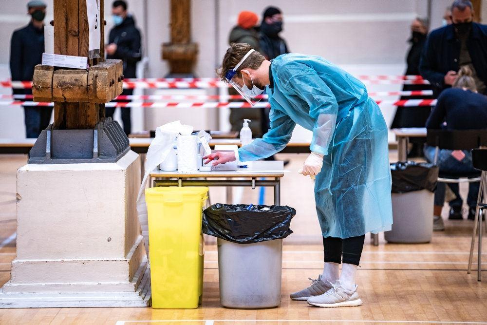 en tester iført blåt plastik forklæde og visir venter på folk at teste.