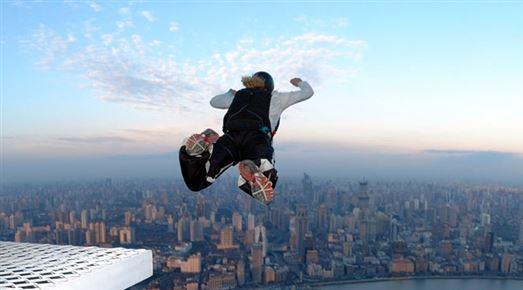 mand hopper ud fra bygning med faldskærm på ryggen