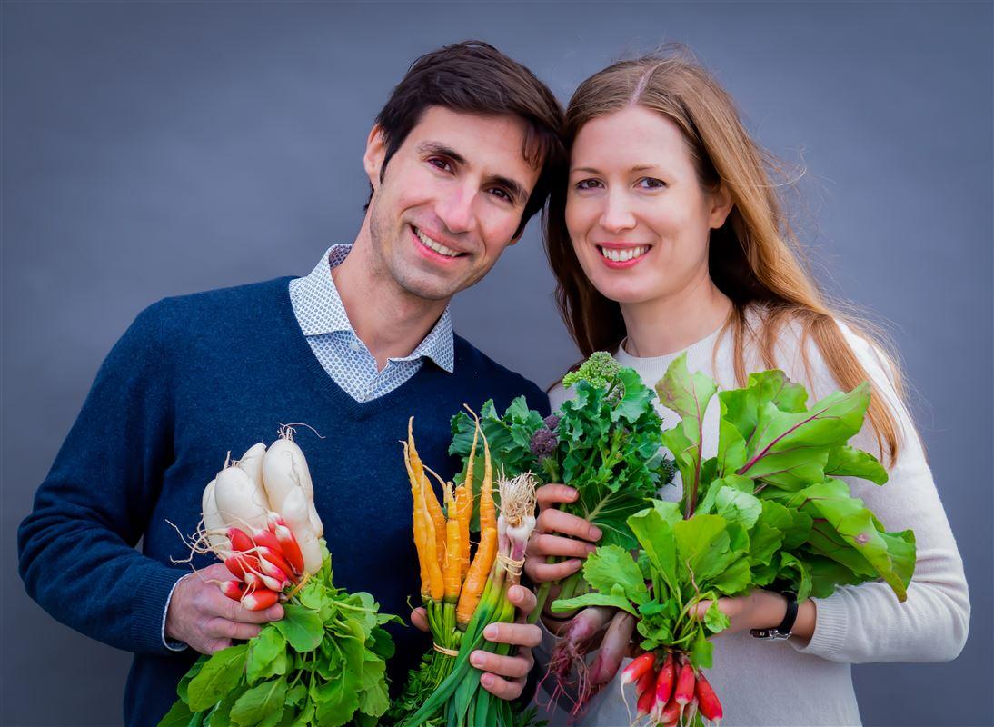Et smilende par med grøntsager i favnen