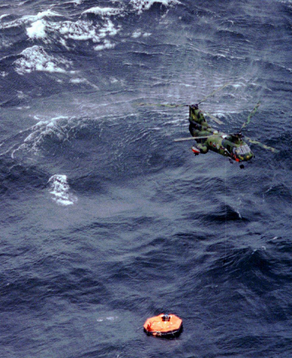 En helikopter svæver over en redningsflåde