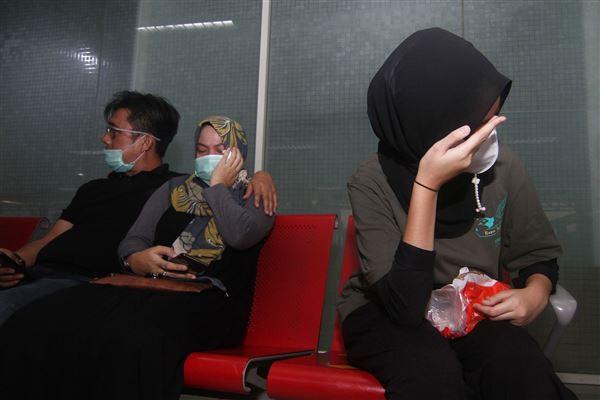 pårørende sidder og venter i lufthavn