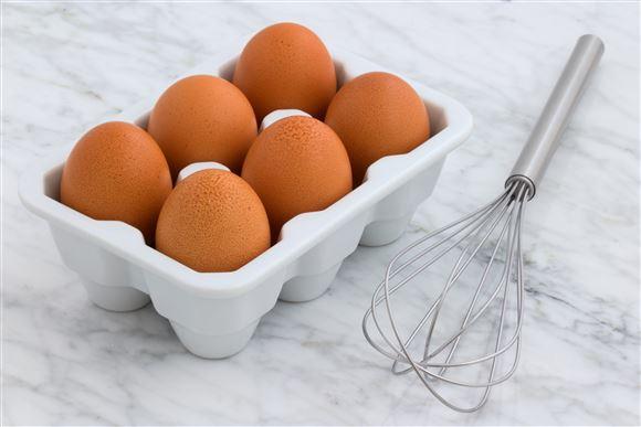 6 æg i bakke med en håndpisker ved siden af