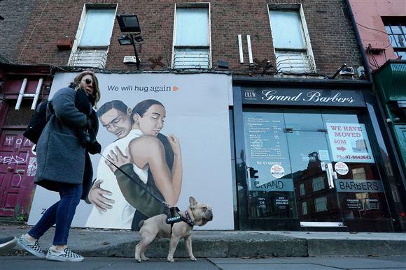 En kvinde lufter sin hund i Dublin foran en plakat med ordlyden: Vi vil kramme igen.